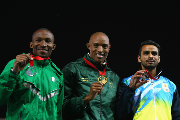 Mokoena is flanked by Tosin Oke (L) and India's Arpinder Singh after winning GOLD in Glasgow. (Photo Credit: Cameron Spencer/Getty Images)